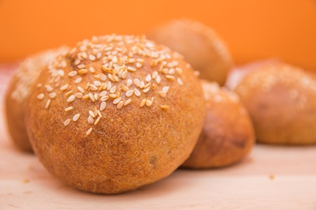 Tasty buns with sesame, on wooden background Imagens