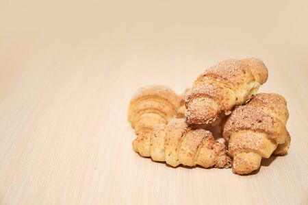 freshly baked croissants on a light wooden table
