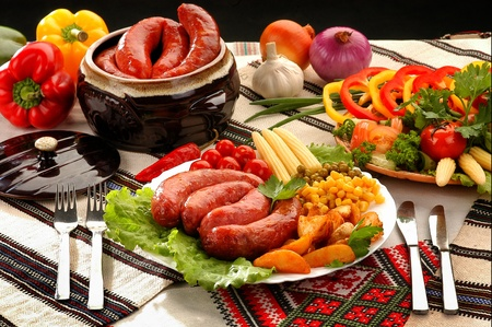 grilled sausages in a pot with fresh vegetables on the table
