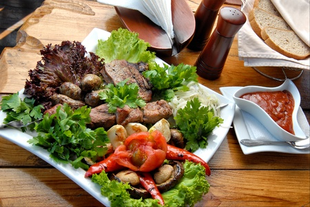 Grilled meat with vegetables, salad and sauce on a plate