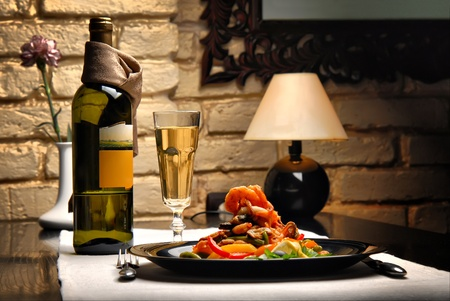 The restaurant interior with served tables, salad a glass of white wine Stock Photo