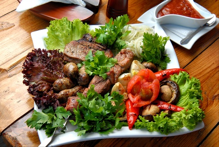 Grilled meat with vegetables, salad and sauce on a plate photo