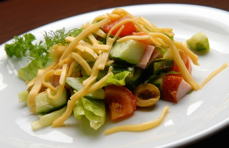 salad with fresh vegetables and cheese, ham and olives on a plate Stock Photo