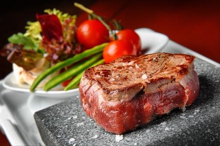 chef cocinando: carne a la parrilla en una piedra con verduras en la placa