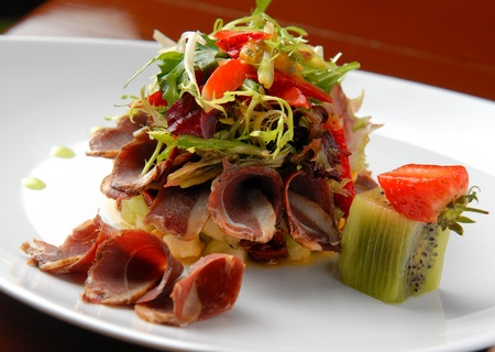 salad with fresh vegetables and smoked duck breast on a plate photo