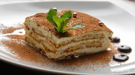 dessert cake with cream and chocolate on a plate