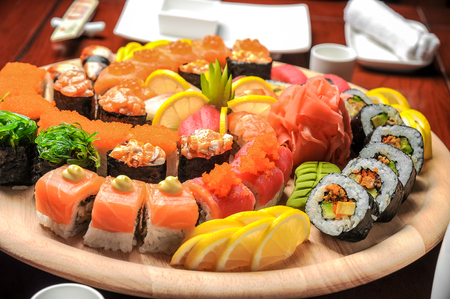 Nigiri sushi and sushi rolls with fish served on wooden table Stock Photo