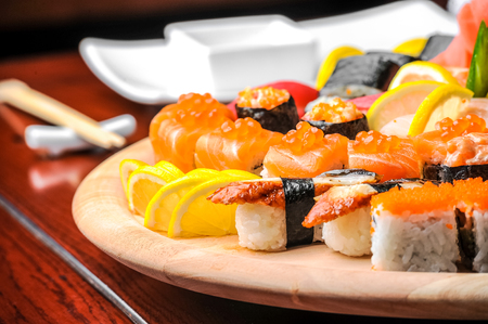 sake: Nigiri sushi and sushi rolls with fish served on wooden table Foto de archivo