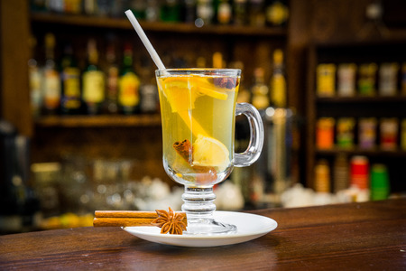 orange peel clove: mulled wine with white wine in the glass on the bar
