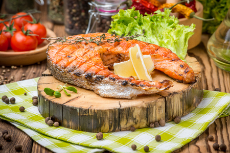 grilled salmon steak on a plate made of wood