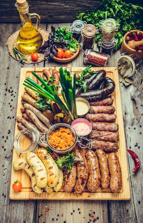 a set of different sausages, grilled on plate, on a wooden background
