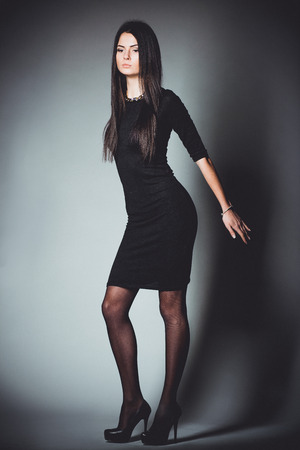 Beautiful, young and emotional girl in studio, on a dark background