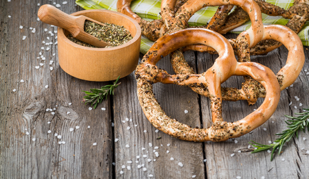 Pretzels on wooden board on rustic background. Spices, olive grass