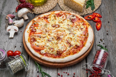 Pizza with tomatoes, mozzarella cheese, black olives and basil. Delicious italian pizza on wooden pizza board. Table top view Stock Photo