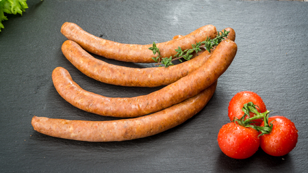 Food background. Snack stick sausages on a wooden table. Smoked sausages