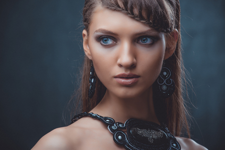Portrait of a beautiful woman with beautiful make-up and hairstyle. With the decoration of a large stone on a black background.