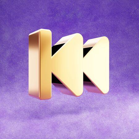 Fast backward icon. Gold glossy Fast backward symbol isolated on violet velvet background.