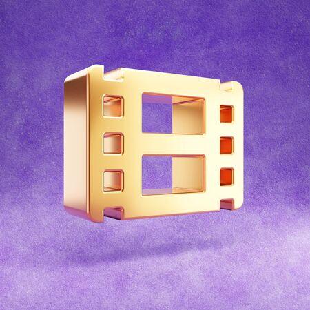 Film icon. Gold glossy Film symbol isolated on violet velvet background.