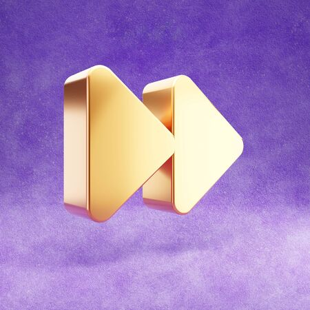 Fast forward icon. Gold glossy Fast forward symbol isolated on violet velvet background.