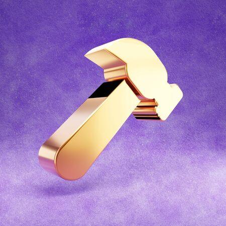 Hammer icon. Gold glossy Hammer symbol isolated on violet velvet background.
