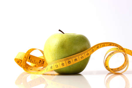 apple and measuring tape close-up on a light background