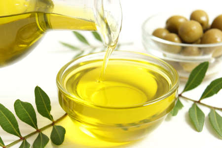 olive oil, green leaves and olives on the table.