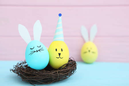 Easter eggs with cute faces and ears on a colored background.