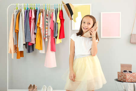 Little cute girl chooses clothes in dressing room