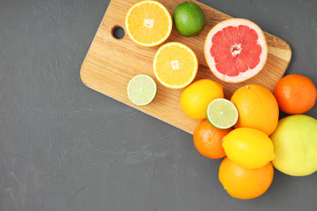 Different citrus and juicy slices on a colored background. Place to insert text.