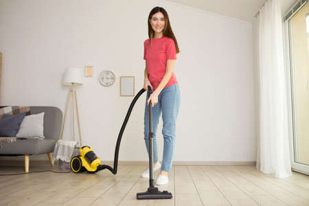 Beautiful young girl in a good mood makes house cleaning with a vacuum cleaner
