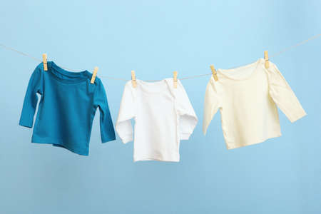 Baby clothes on a rope on a colored background. Stock Photo