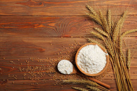 Wheat flour and spikelets of wheat on a light background