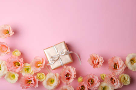 flower arrangement and gift on colored background top view with place for text