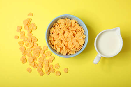 Golden and crunchy cornflakes on a colored background close-up Фото со стока