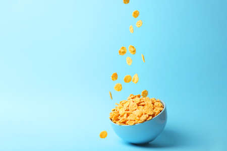 Delicious cornflakes falling into a plate on a colored background. Фото со стока