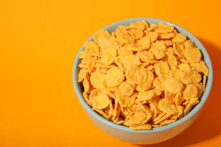 Delicious cornflakes in a plate against colored background. Фото со стока