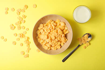 Crispy cornflakes with milk for breakfast on a colored background close-up.