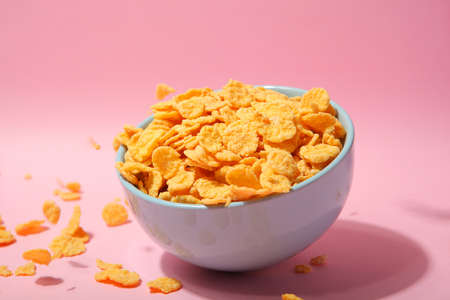 Delicious cornflakes in a plate against colored background. . High quality photo Фото со стока