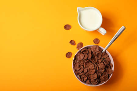 chocolate cornflakes for breakfast on colored background close up