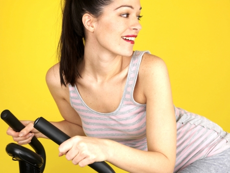 Young Woman Using Exercise Bike. Model Released photo