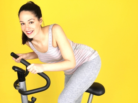 silliness: Young Woman Using Exercise Bike. Model Released