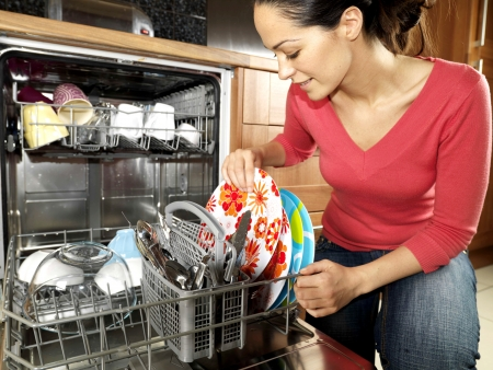 Woman Emptying  Filling Dishwasher Stock Photo