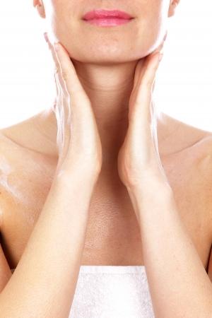Giovane donna applicare crema corpo