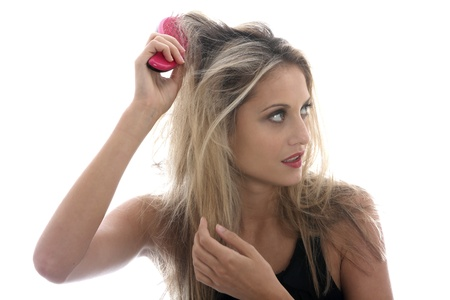 knotted: Model Released. Young Woman Brushing Tangled Hair Stock Photo