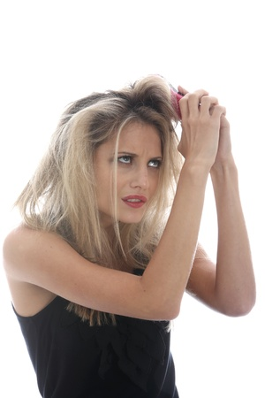 bad hair day: Model Released. Young Woman Brushing Tangled Hair Stock Photo