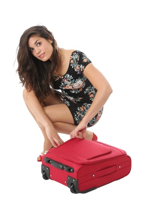 Model Released. Attractive Young Woman Doing Up Suitcase photo