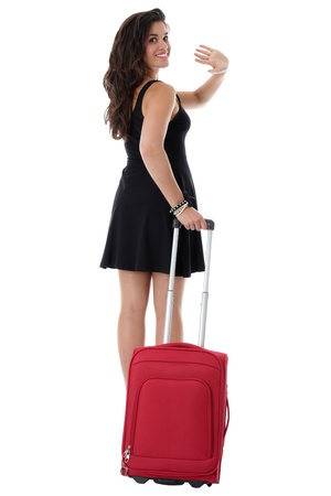 Model Released. Attractive Young Woman Pulling a Red Suitcase Waving photo