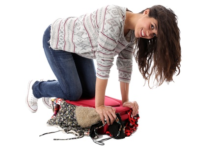 Model Released. Young Woman Packing a Red Suitcase Stock Photo - 21482530