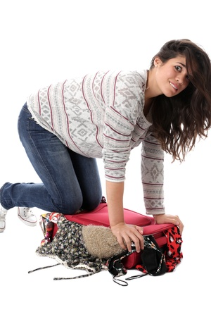 Model Released. Young Woman Packing a Red Suitcase photo
