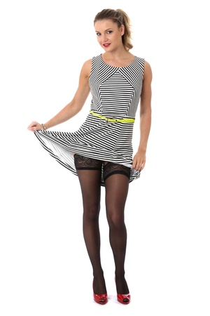 Model Released. Sexy Young Woman Raising Skirt Showing Stocking Tops Stock Photo